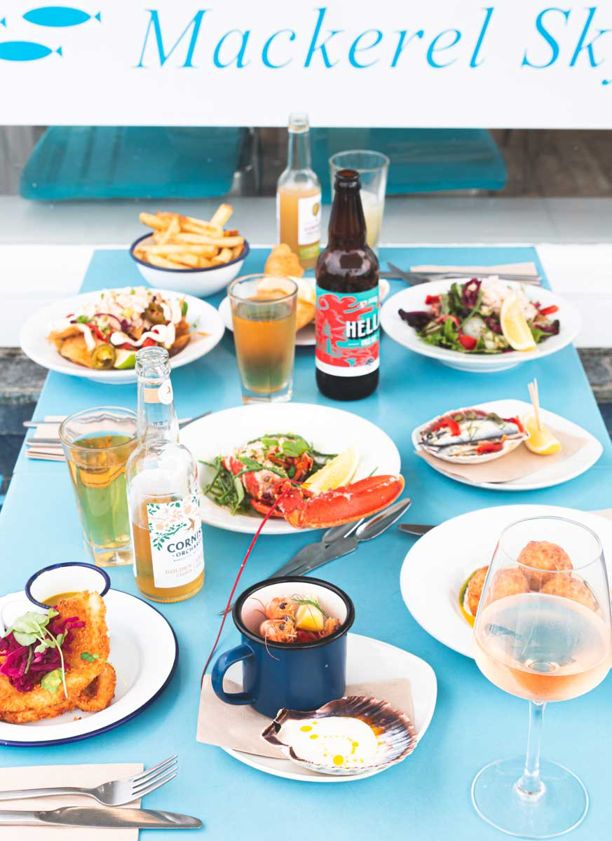Seafood spread with drinks, on our blue tables outside.