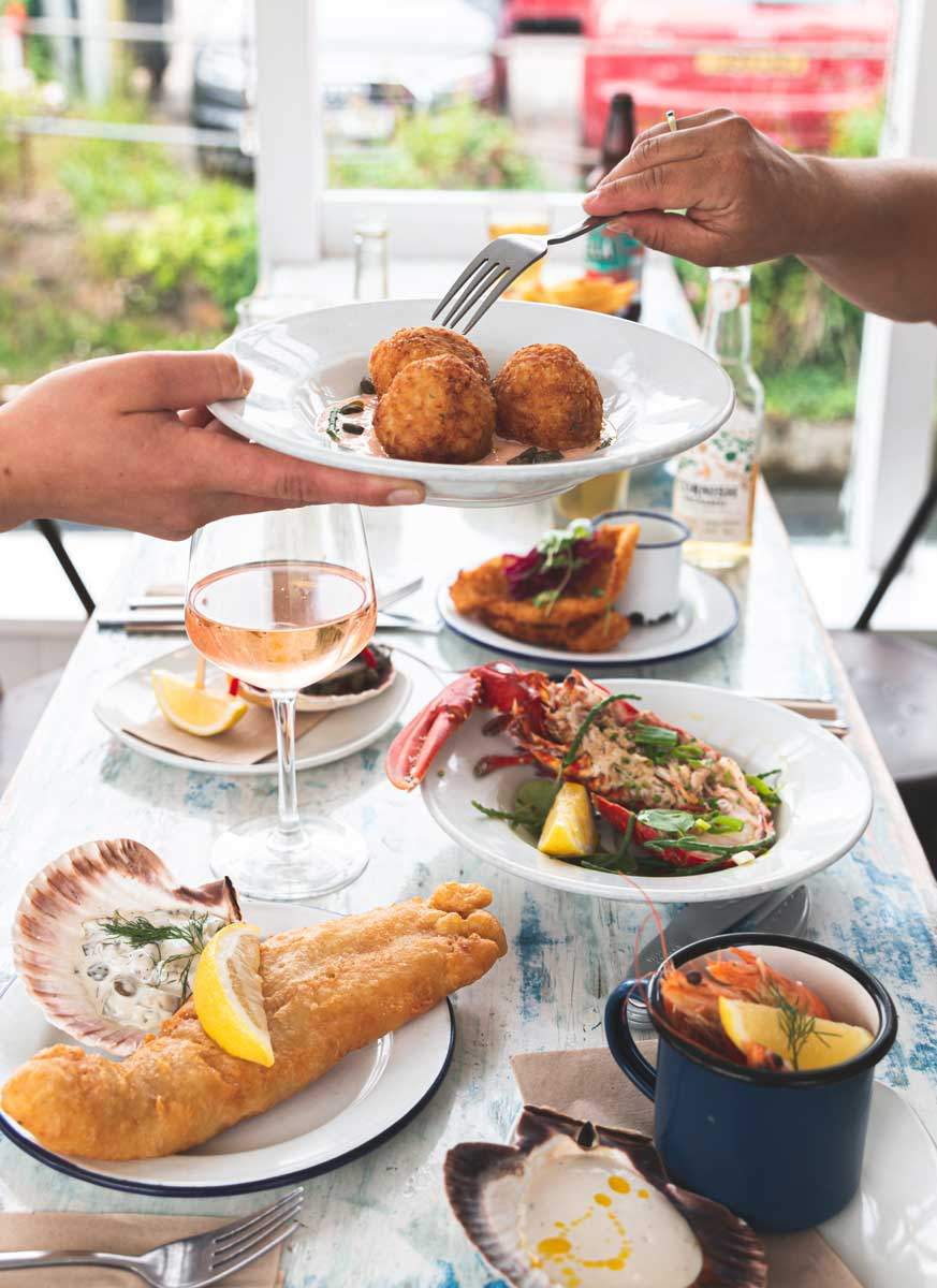 Picking up arancini balls with a fork, and a selection of seafood dishes.
